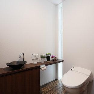 他の地域のコンテンポラリースタイルのおしゃれなトイレ・洗面所 (フラットパネル扉のキャビネット、濃色木目調キャビネット、白い壁、ベッセル式洗面器、木製洗面台、茶色い床、ブラウンの洗面カウンター、壁掛け式トイレ) の写真