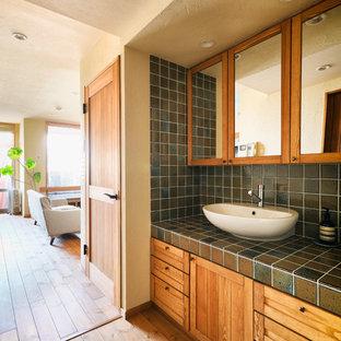 Ejemplo de aseo asiático con armarios con paneles empotrados, puertas de armario de madera oscura, paredes beige, suelo de madera en tonos medios, lavabo sobreencimera, encimera de azulejos y suelo marrón