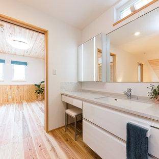 Modelo de aseo asiático con armarios con paneles lisos, puertas de armario blancas, paredes blancas, suelo de madera clara, suelo beige y encimeras grises