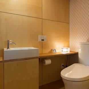 Imagen de aseo de estilo zen con puertas de armario de madera oscura, lavabo sobreencimera, suelo beige, armarios con paneles lisos, paredes marrones, encimera de madera y encimeras marrones