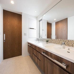 コンテンポラリースタイルのおしゃれなトイレ・洗面所 (フラットパネル扉のキャビネット、濃色木目調キャビネット、マルチカラーのタイル、白い壁、一体型シンク、ベージュの床、白い洗面カウンター) の写真