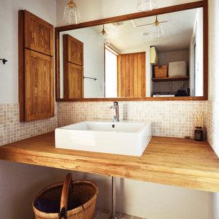 他の地域のアジアンスタイルのおしゃれなトイレ・洗面所 (ベージュのタイル、ベージュの壁、ベッセル式洗面器、木製洗面台、茶色い床、ブラウンの洗面カウンター) の写真