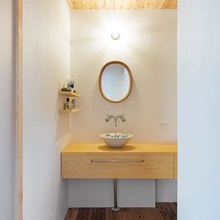 Modelo de aseo asiático, grande, con puertas de armario de madera oscura, paredes blancas, suelo de madera en tonos medios, lavabo sobreencimera, encimera de madera y suelo beige