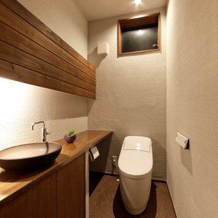 他の地域のおしゃれなトイレ・洗面所 (茶色いキャビネット、一体型トイレ、グレーの壁、オーバーカウンターシンク、木製洗面台、茶色い床、ブラウンの洗面カウンター、塗装板張りの天井、塗装板張りの壁) の写真