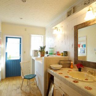 東京23区のヴィクトリアン調のおしゃれなトイレ・洗面所 (茶色いキャビネット、淡色無垢フローリング、オーバーカウンターシンク、タイルの洗面台、茶色い床、白い壁) の写真