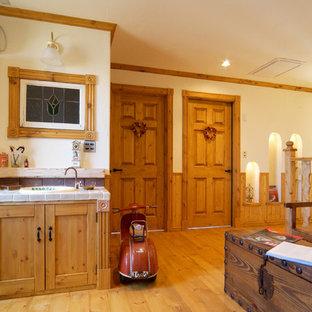 Идея дизайна: туалет в викторианском стиле с коричневыми фасадами, белыми стенами, светлым паркетным полом, накладной раковиной, столешницей из плитки и коричневым полом