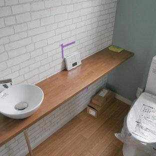 Идея дизайна: маленький туалет в морском стиле с белой плиткой, синими стенами, полом из травертина, накладной раковиной, коричневым полом и коричневой столешницей
