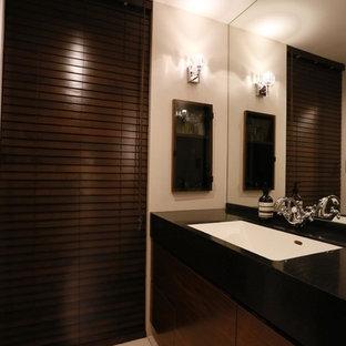 他の地域のモダンスタイルのトイレ・洗面所の画像 (フラットパネル扉のキャビネット、濃色木目調キャビネット、白い壁、一体型シンク、白い床)