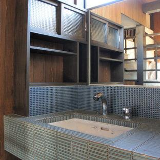 他の地域の中くらいのカントリー風おしゃれなトイレ・洗面所 (ガラス扉のキャビネット、茶色いキャビネット、青いタイル、モザイクタイル、茶色い壁、濃色無垢フローリング、アンダーカウンター洗面器、タイルの洗面台、茶色い床、青い洗面カウンター、造り付け洗面台、板張り天井、板張り壁) の写真
