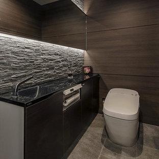 Cette photo montre un WC et toilettes moderne avec un placard à porte plane, des portes de placard marrons, un WC à poser, un sol gris, un plan de toilette noir et un mur marron.