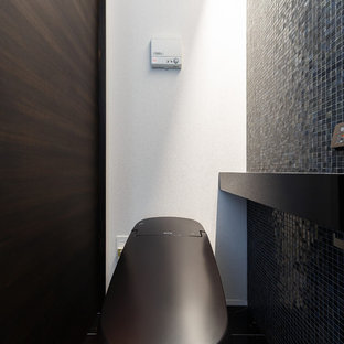 Idée de décoration pour un très grand WC et toilettes minimaliste avec des portes de placard noires, un carrelage noir, carrelage en mosaïque et un plan de toilette noir.