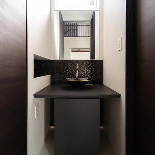 Cette photo montre un très grand WC et toilettes moderne avec des portes de placard noires, un WC à poser, un carrelage noir, carrelage en mosaïque, un sol en carrelage de céramique, un sol blanc et un plan de toilette noir.