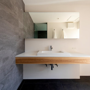Cette photo montre un WC et toilettes de taille moyenne avec un placard sans porte, des portes de placard blanches, un mur beige, une vasque, un plan de toilette en bois, un sol noir, un plan de toilette marron et meuble-lavabo encastré.