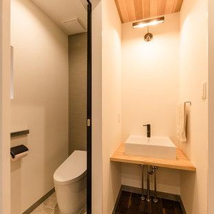 他の地域の小さいモダンスタイルのおしゃれなトイレ・洗面所 (白い壁、濃色無垢フローリング、ベッセル式洗面器、木製洗面台、茶色い床、ベージュのカウンター) の写真