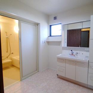 他の地域のトランジショナルスタイルのおしゃれなトイレ・洗面所 (白いキャビネット、白い壁、クッションフロア、ピンクの床) の写真