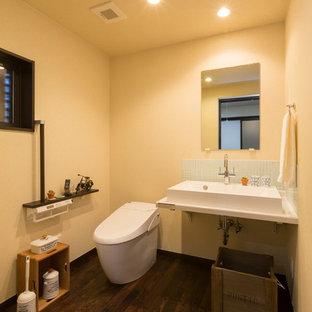 Imagen de aseo asiático con paredes beige, suelo de madera oscura, lavabo tipo consola y suelo marrón