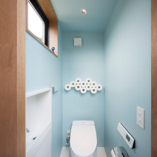 Diseño de aseo minimalista con sanitario de una pieza, suelo vinílico, lavabo suspendido, suelo blanco, paredes azules, armarios con paneles lisos y puertas de armario blancas