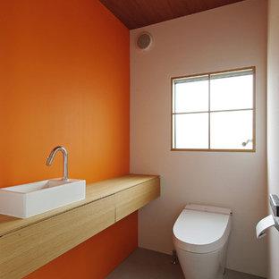 Diseño de aseo actual con armarios con paneles lisos, puertas de armario de madera clara, sanitario de pared, parades naranjas, suelo de cemento, lavabo sobreencimera, encimera de madera, suelo gris y encimeras beige