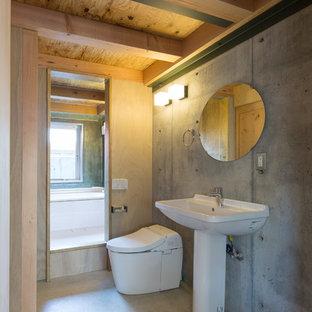 Diseño de aseo de estilo zen, pequeño, con armarios abiertos, sanitario de una pieza, paredes grises, suelo de cemento, lavabo con pedestal, suelo gris y encimeras blancas