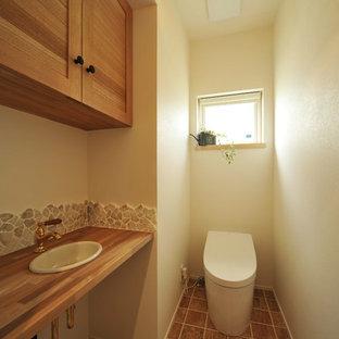 他の地域のアジアンスタイルのおしゃれなトイレ・洗面所 (落し込みパネル扉のキャビネット、中間色木目調キャビネット、白い壁、木製洗面台、茶色い床、ブラウンの洗面カウンター) の写真
