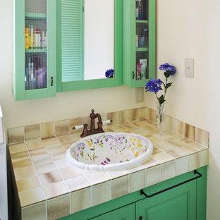 Стильный дизайн: туалет в стиле современная классика с фасадами с утопленной филенкой, зелеными фасадами, белыми стенами, накладной раковиной и столешницей из плитки - последний тренд