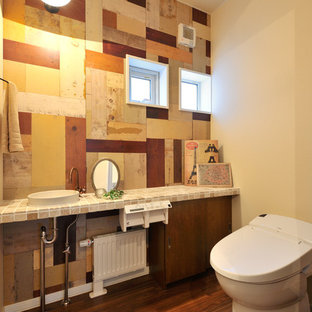 Photo of a world-inspired cloakroom in Sapporo with flat-panel cabinets, medium wood cabinets, brown tiles, beige tiles, multi-coloured walls, medium hardwood flooring, a built-in sink and brown floors.