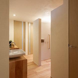 Imagen de aseo asiático, de tamaño medio, con paredes blancas, suelo de madera en tonos medios y suelo rosa