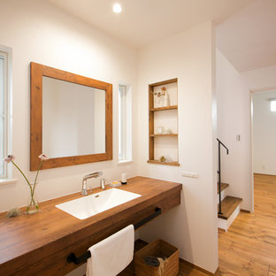 Imagen de aseo asiático con paredes blancas, suelo de madera en tonos medios, encimera de madera, suelo marrón y encimeras marrones