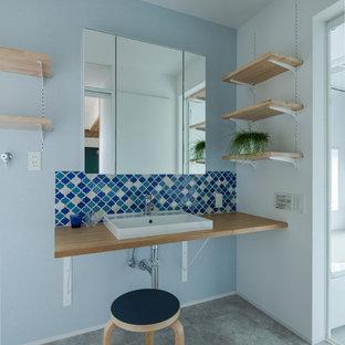 他の地域のインダストリアルスタイルのおしゃれなトイレ・洗面所 (青い壁、コンクリートの床、ベッセル式洗面器、木製洗面台、グレーの床、ブラウンの洗面カウンター) の写真