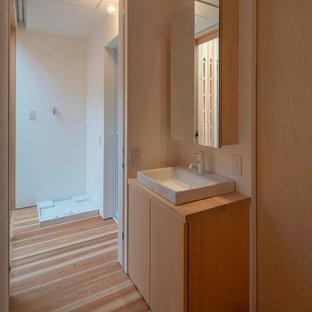Пример оригинального дизайна: маленький туалет в восточном стиле с фасадами с декоративным кантом, бежевыми фасадами, столешницей из дерева, белой столешницей, белыми стенами, паркетным полом среднего тона, накладной раковиной и бежевым полом