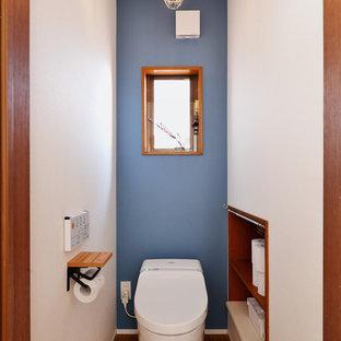 Foto di un bagno di servizio etnico con pareti multicolore, pavimento in legno verniciato e pavimento marrone