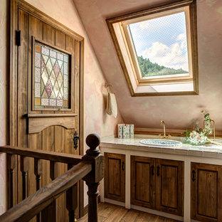 Esempio di un bagno di servizio shabby-chic style con ante con riquadro incassato, ante con finitura invecchiata, pareti rosa, pavimento in legno massello medio, lavabo da incasso, top piastrellato, pavimento marrone e top beige
