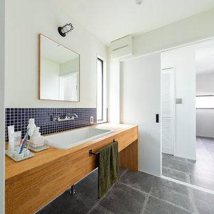 Cette image montre un WC et toilettes urbain de taille moyenne avec un placard sans porte, des portes de placard en bois brun, un carrelage bleu et un plan de toilette marron.