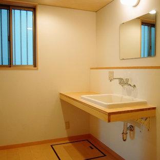 Cette image montre un petit WC et toilettes nordique avec des portes de placard en bois clair, un mur blanc, un sol en contreplaqué, un lavabo posé, un plan de toilette en bois, un sol beige et un plan de toilette beige.