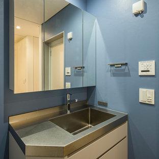 Esempio di un bagno di servizio minimal con ante lisce, ante grigie, pavimento in linoleum, lavabo integrato, top in acciaio inossidabile e pavimento grigio
