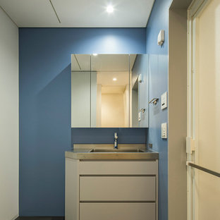 Стильный дизайн: туалет в современном стиле с плоскими фасадами, серыми фасадами, полом из линолеума, столешницей из нержавеющей стали, серым полом и монолитной раковиной - последний тренд