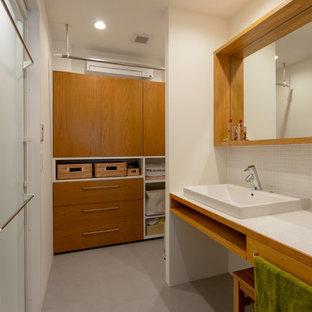 東京23区のコンテンポラリースタイルのおしゃれなトイレ・洗面所 (白いタイル、磁器タイル、タイルの洗面台、グレーの床、白い洗面カウンター、白い壁) の写真