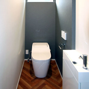 Пример оригинального дизайна: туалет в стиле модернизм с фасадами с декоративным кантом, белыми фасадами, унитазом-моноблоком, синими стенами, полом из ламината, столешницей из искусственного камня, коричневым полом и белой столешницей
