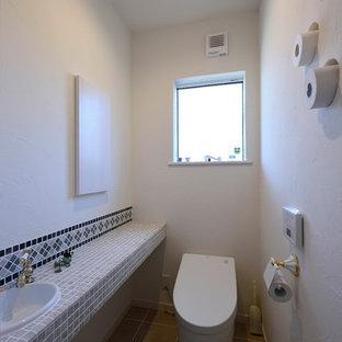 他の地域の小さい地中海スタイルのおしゃれなトイレ・洗面所 (白い壁、オーバーカウンターシンク、ベージュの床) の写真