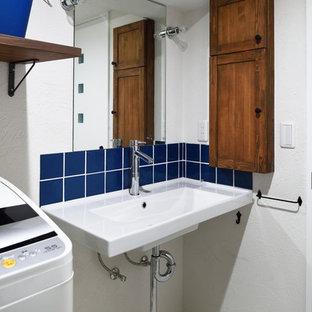 他の地域の小さいアジアンスタイルのおしゃれなトイレ・洗面所 (落し込みパネル扉のキャビネット、中間色木目調キャビネット、白い壁、白い床) の写真