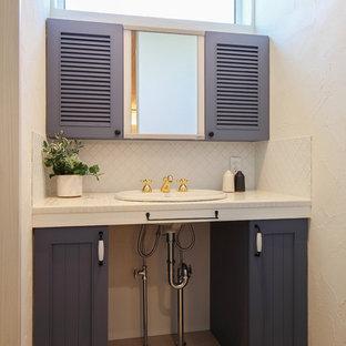 他の地域のミッドセンチュリースタイルのおしゃれなトイレ・洗面所 (落し込みパネル扉のキャビネット、青いキャビネット、白い壁、ベッセル式洗面器、ベージュの床) の写真