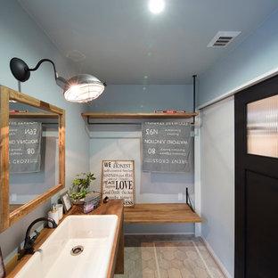 他の地域のミッドセンチュリースタイルのおしゃれなトイレ・洗面所 (青い壁、オーバーカウンターシンク、グレーの床) の写真