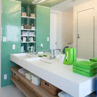 Пример оригинального дизайна: туалет в современном стиле с монолитной раковиной, открытыми фасадами, светлыми деревянными фасадами, зеленой плиткой, плиткой мозаикой, разноцветными стенами и белой столешницей
