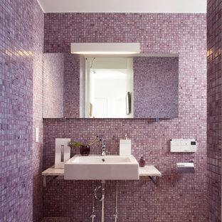 Новый формат декора квартиры: туалет в современном стиле с плиткой мозаикой, фиолетовыми стенами, настольной раковиной, розовой плиткой и белой столешницей