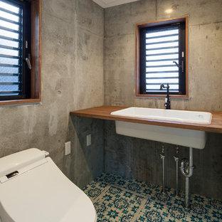 東京23区の中くらいのインダストリアルスタイルのおしゃれなトイレ・洗面所 (一体型トイレ、グレーの壁、磁器タイルの床、オーバーカウンターシンク、木製洗面台、青い床、白い洗面カウンター) の写真