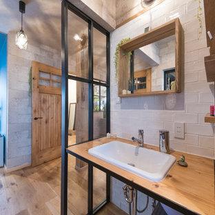 東京都下のインダストリアルスタイルのおしゃれなトイレ・洗面所 (オープンシェルフ、濃色木目調キャビネット、白いタイル、磁器タイル、青い壁、磁器タイルの床、グレーの床、ブラウンの洗面カウンター) の写真