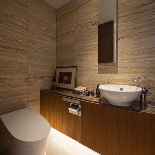 Idee per un bagno di servizio etnico con ante lisce, ante in legno scuro, pareti marroni, lavabo a bacinella, top in marmo, pavimento bianco e top marrone