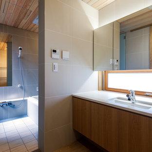 Immagine di un bagno di servizio nordico con consolle stile comò, ante marroni, piastrelle beige, piastrelle di pietra calcarea, pareti beige, pavimento in legno massello medio, lavabo integrato, top in superficie solida, pavimento marrone e top bianco