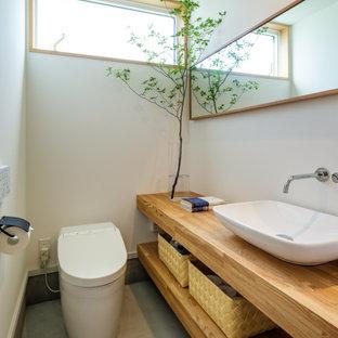 Réalisation d'un WC et toilettes asiatique avec un placard sans porte, des portes de placard en bois brun, un WC à poser, un mur blanc, béton au sol, une vasque, un plan de toilette en bois, un sol gris, un plan de toilette marron et meuble-lavabo suspendu.