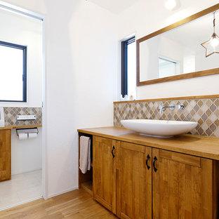 他の地域のカントリー風おしゃれなトイレ・洗面所 (フラットパネル扉のキャビネット、ヴィンテージ仕上げキャビネット、白い壁、無垢フローリング、ベッセル式洗面器、茶色い床) の写真